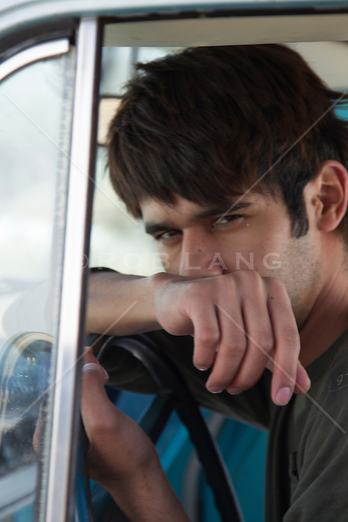 young man in sitting in a car with a mysterious look on his face