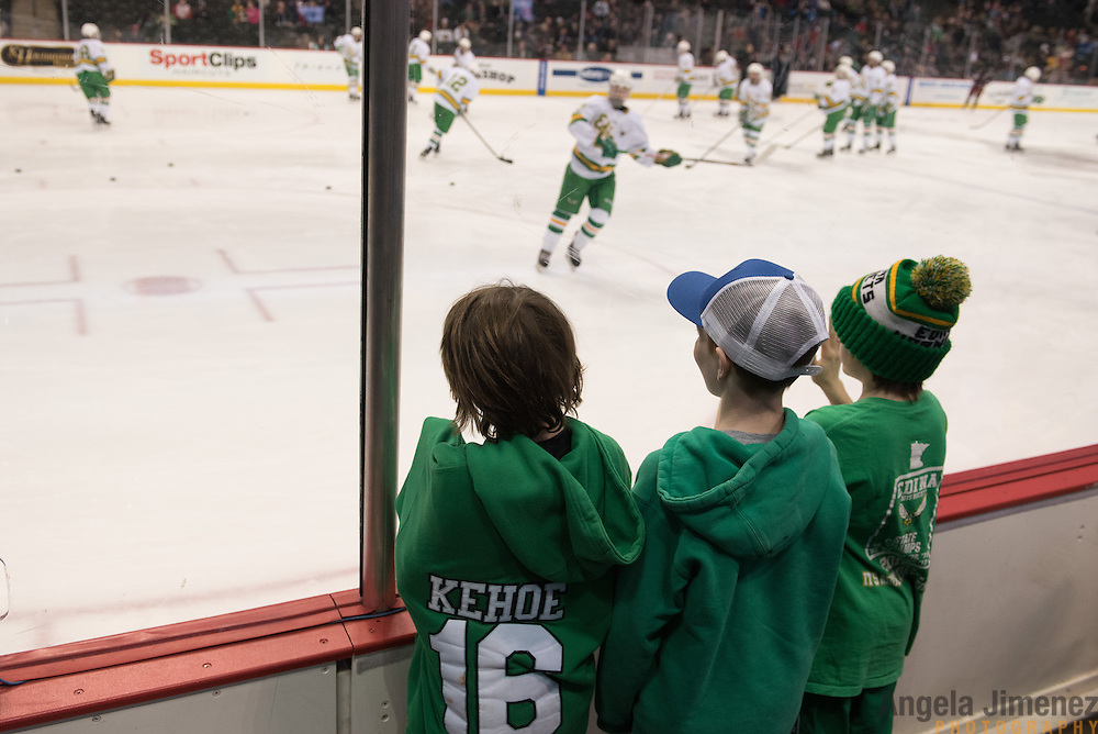 Young Edina hockey players Hamilton Kehoe, 9, from left, Tommy Sieve, 10, and Sean Burns, 9, watch Edina players warm up before the Class AA semifinal game between Duluth East and Edina (Duluth East won 3-1) at the Minnesota State High School League Boys' State Hockey Tournament at the Xcel Energy Center in St. Paul, Minnesota on March 6, 2015. <br />  <br /> <br /> Photo by Angela Jimenez for Minnesota Public Radio www.angelajimenezphotography.com