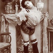 Woman posing warming her rear end against a fireplace.  Vintage French erotic postcard circa 1910
