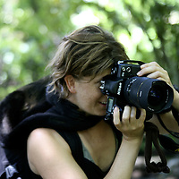 Central America, Latin America, Costa Rica. A photographer focuses despite the Spider Monkey wrapped around her neck.