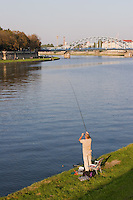 man seen fishing in sunshine on the banks of the vistula river with pilsudski bridge and podgorze behind.