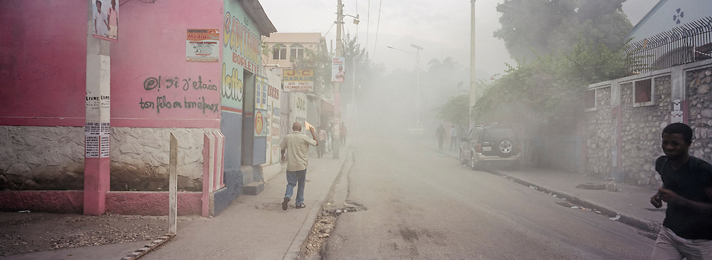 Smoke lingers in the street after police put out a pile of burning tires and debris during an anti-government protest on Tuesday, December 16, 2014 in Port-au-Prince, Haiti. President Michel Martelly was elected in 2010 with great hope for reforms, but in the wake of slow recovery and parliamentary elections that are three years overdue, his popularity has suffered tremendously, forcing Prime Minister Laurent Lamothe to resign.