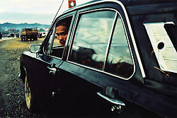 A Laotian man sitting in a parked black car looks out the window behind him towards the camera. The mountainous landscape is visible in the background, Northern Laos, Southeast Asia