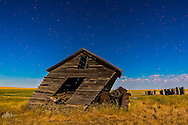 A rustic and tilted farm shed and tractor on an abandoned farmyard near Bow Island, Alberta, with illumination from an almost Full Moon, July 30, 2015. The bowl of the Big Dipper is at upper left. This is a single frame from a 300-frame panning time-lapse.