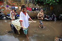 Children using a cart to deliver drinking water to houses on a flooded street, Tallo, Sulawesi, Indonesia.