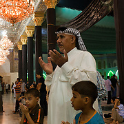 A Shi'a Muslim father and his two sons say prayers together at the Khadamiyah Shrine September 04, 2010 in Baghdad, Iraq. An intense power struggle between Iraq's Shia political leaders and parties is one of the main obstacles to the formation of a new government since the inconclusive March 2010 poll, according to senior Iraqi officials involved in ongoing negotiations. Credit: Scott Nelson for the Wall Street Journal.Slug: Iraq - Shia divisions.