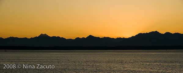 Olympic Mountains in silhouette against a Pacific ocean sunset.