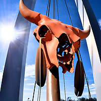Wichita, Kansas Composite of Two Photos<br /> Two photos of Wichita, Kansas are: 1) The arch of a pedestrian bridge over the Big Arkansas River; and 2) A long-horn cattle skull with Indian feathers. Both are located near the &ldquo;Keeper of the Plains&rdquo; sculpture and plaza.