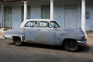 Grey and white car in front of a grey and white building in San Juan y Martinez, Pinar del Rio, Cuba.