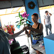 Gloria Jaimez, an employee at Marioly's Flowers in Shed 3 at the Dallas Farmers Market, sells two stems of lilies to Yesenia Delgado September 2, 2010.  Shop owner Enrique Perez (not pictured) is not sure what to think of plans to privatize the market because that idea has been discussed for years.  He wonders how long it will take for any changes to occur.  (Courtney Perry/The Dallas Morning News) 09032010xMETRO 09032010xBRIEFING