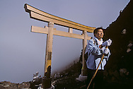 Climber passing through the final gate or tori at the summit of Mt. Fuji. For many, the mountain has religious significance.