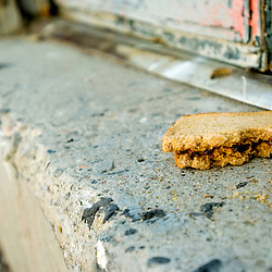 A half eaten peanut butter and jelly sandwich sits on a step in an alleyway in Gallup, New Mexico.