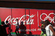 Visitors walk past a coca-cola advertisement on the way to a technical rehearsal for the Olympic Opening Ceremony for the 2012 Olympic Games, at the Olympic stadium, London.