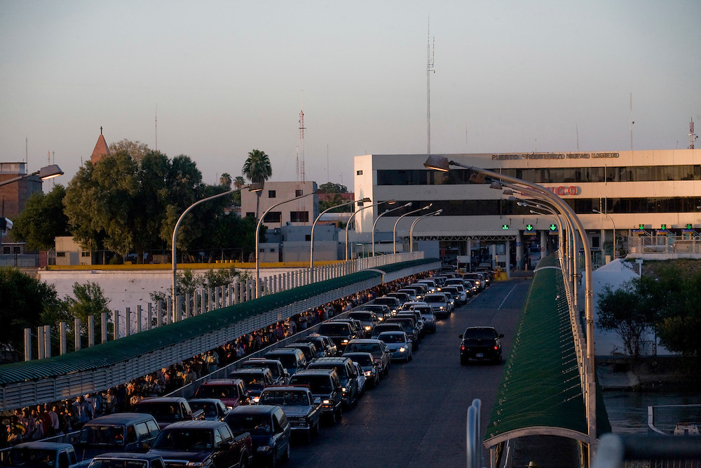 Cars and pedestrians line up to enter the United States on August 20, 2010 as traffic into Mexico is relatively empty in Laredo, Texas. City officials say negative attitudes about the city's more dangerous sister Nuevo Laredo have kept tourists from coming and effected the over all economics of the town.