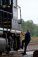 A railroad conductor working for the Norfolk Southern climbs aboard his train after lining a switch at the yard in Pine Junction, IN.