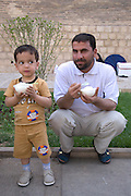 Iranian man and his son eat ice cream Shiraz, Iran