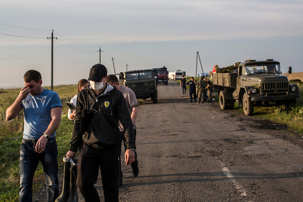GRABOVO, UKRAINE - JULY 19: People leave the scene of the crash of Malaysia Airlines flight MH 17 as emergency personnel remove the bodies of passengers after pro-Russia separatist fighters established control of the site on July 19, 2014 in Grabovo, Ukraine. Malaysia Airlines flight MH17 was travelling from Amsterdam to Kuala Lumpur when it crashed killing all 298 on board including 80 children. The aircraft was allegedly shot down by a missile and investigations continue over the perpetrators of the attack. (Photo by Brendan Hoffman/Getty Images) *** Local Caption ***