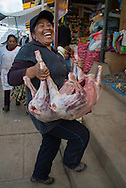 Woman carries pig for sale at market, Lake Titicaca, Peru