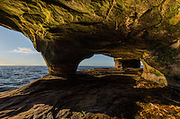 Evening light illuminates a lakeside cave along the Lake Superior shore<br />