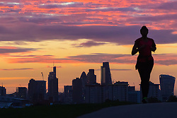 Primrose Hill, London, September 27th 2016. A runner  on Primrose Hill's silhouette looms over the backdrop of the City's skyscrapers as dawn breaks over London. &copy;Paul Davey<br /> FOR LICENCING CONTACT: Paul Davey +44 (0) 7966 016 296 paul@pauldaveycreative.co.uk