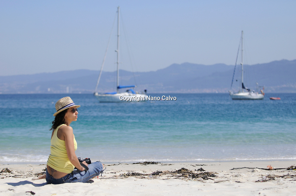 Young woman in Rodas Beach (Praia das Rodas) in Cies Islands (Islas C&iacute;es), a paradisiac archipelago and Natural Reserve since 1908, off the coast of Pontevedra, in Galicia, Spain. <br /> <br /> In the year 2007, the British newspaper The Guardian chose this beach, in the island of Monteagudo, as the &quot;most beautiful beach of the world&quot;.