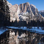 Yosemite Falls, framed by winter ice, is reflected in the Merced River in Yosemite National Park, California. With a height of 2,425 feet (739 meters), Yosemite Falls is the highest measured waterfall in North America and the fifth-highest in the world.
