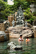 """Bathers in the mixed """"Maka no yu"""" (larger hot spring) of the Takaragawa onsen (hot spring) in Gunma prefecture north of Tokyo. The founder of the onsen was a Buddhist and there are many Buddhist statues around and inside the hot springs. - JAPAN 8 July 2006"""