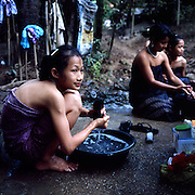 """Karen women doing their laundry and taking a bath next to a well inside Mae La refugee camp..Burmese refugee camp """"Mae La"""" is north of border-town Mae Sot and lies along the Thai-Burmese border on the side of Thailand. Approximately 50,000 people live there. 38,167 was the official number of registered people in November 2009, according to the Thailand Burma Border Consortium (TBBC), and the rest are unregistered or people who come and go."""