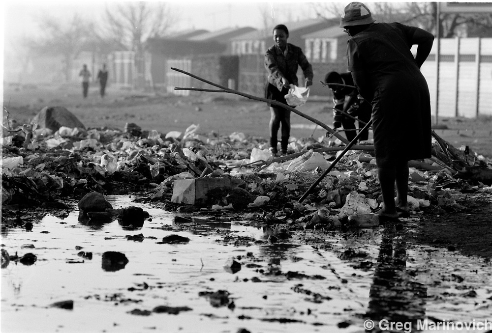 Reisdents clean up from overspilling sewerage in Sebokeng some 65 km south of Johannesburg, South Africa 1993. (Photo by Greg Marinovich)