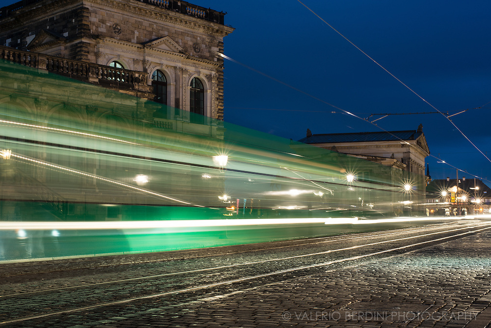 A tram passes on Sophienstrasse in Dresden at the blue hour