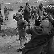 <<coal distribution photo package>>..A fight breaks out between two young boys who were collecting scraps of coal as is fell from an ICRC (International Committe for the Red Cross) distribution truck inside Kabul city.(shot 2-11-02)