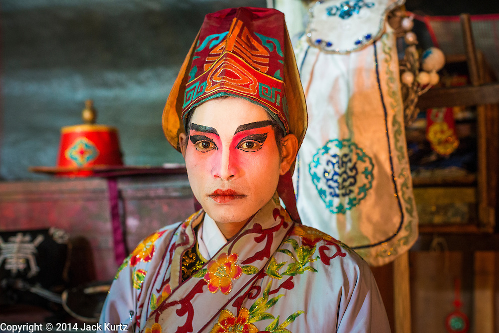 """25 JANUARY 2014 - BANG LUANG, NAKHON PATHOM, THAILAND: A performer with the Sing Tong Teochew opera troupe relaxes backstage during a show in a Chinese shrine in the town of Bang Luang, Nakhon Pathom, Thailand. The Sing Tong Teochew opera troupe has been together for 60 years and travels through central Thailand and Bangkok performing for mostly ethnic Chinese audiences. Chinese opera was once very popular in Thailand, where it is called """"Ngiew."""" It is usually performed in the Teochew language. Millions of Chinese emigrated to Thailand (then Siam) in the 18th and 19th centuries and brought their cultural practices with them. Recently the popularity of ngiew has faded as people turn to performances of opera on DVD or movies. There are still as many 30 Chinese opera troupes left in Bangkok and its environs. They are especially busy during Chinese New Year when travel from Chinese temple to Chinese temple performing on stages they put up in streets near the temple, sometimes sleeping on hammocks they sling under their stage.     PHOTO BY JACK KURTZ"""