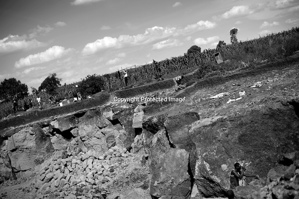 Workers dig in an unregulated quarry for stones to be used for construction outside of Nairobi, Kenya June 5, 2008. A building and construction boom has shot up the demand for building materials, leading to high demand for building stones, ballast and sand. A delay in the review of a Kenyan mining Act has led to the proliferation of new and unregulated quarrying activities in forrest areas and private farm land. According to the National Environmental Management Authority (Nema), of the hundreds of quarries operating in central Kenya only two private quarries conduct an annual audit or have met the country's environments assessment impacts (EAI) requirements. PHOTO BY KEITH BEDFORD