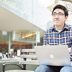 Portrait photograph of young man with Apple Macbook Air Mac laptop contenplating the future
