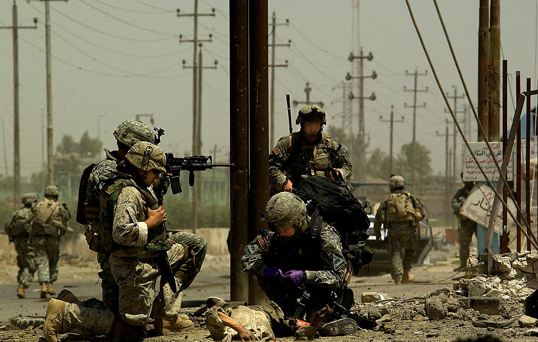 Medic SPC John Schroeder treats an injured Iraqi man lying in the street after a suicide car bomb explosion at an intersection in Tameem, Ramadi, Iraq on August 10, 2006. The soldiers from Bravo Company 2-6 Infantry, Task Force 1-35 from Baumholder Germany, were performing a routine patrol at an intersection in Tameem, a suburb of Ar Ramadi when a suicide car bomb exploded about twenty five meters in front of the patrol. Initial reports indicated that two were killed (one civilian and the bomber) and four were wounded (one Iraqi Police Officer and three civilians). Immediately after the explosion, Soldiers of Bravo Company cordoned off the area, treated and evacuated the wounded and maintained security until an Explosive Ordinance Disposal team (EOD) arrived to clear the area.  One civilian died of wounds at the treatment facility.  While EOD was on scene, the patrol took small arms fire from outside of the cordon.  EOD recovered one 110mm artillery round and three 115mm rounds that were believed to be connected with detonation wires from the dashboard of the vehicle. — © TSgt Jeremy Lock/