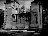 Boy kicks a ball against the side of the earthquake-tested cathedral on Oaxaca's Zocalo, Mexico.