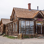 """Prominent windows front the home of James Stuart Cain, who was eventually the principal property owner in Bodie, which is now California's official state gold rush ghost town. Jessie McGath built this house for his new wife in 1879. In the 1890s, JS Cain bought it to live there with his wife until the 1940s. Cain moved to Bodie when he was 25 and built an empire starting with putting lumber barges on Mono Lake and transporting timber to support mine shafts, stoke boilers for machinery, build & heat buildings, and cook food. Cain and a business partner leased a block of land from the Standard Consolidated Mining Company which yielded $90,000 in gold in just 90 days. Cain eventually took control of the Stamp Mill though court action and went on to be one of the richest men in town. Bodie State Historic Park lies in the Bodie Hills east of the Sierra Nevada mountain range in Mono County, near Bridgeport, California, USA. After W. S. Bodey's original gold discovery in 1859, profitable gold ore discoveries in 1876 and 1878 transformed """"Bodie"""" from an isolated mining camp to a Wild West boomtown. By 1879, Bodie had a population of 5000-7000 people with 2000 buildings. At its peak, 65 saloons lined Main Street, which was a mile long. Bodie declined rapidly 1912-1917 and the last mine closed in 1942. Bodie became a National Historic Landmark in 1961 and Bodie State Historic Park in 1962."""