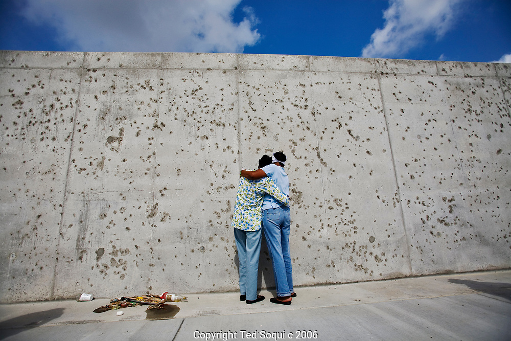 Sisters Celia Nunnery and Carolyn Rae (lt) hold each other at the new Industrial Canal Levee..Citizens of the 9th Ward of New Orleans marched over the two bridges over the industrial canal to commemorate the Hurricane Katrina disaster one year ago today..Residents of the Lower 9th threw flowers into the canal and then marched into Downtown New Orleans..