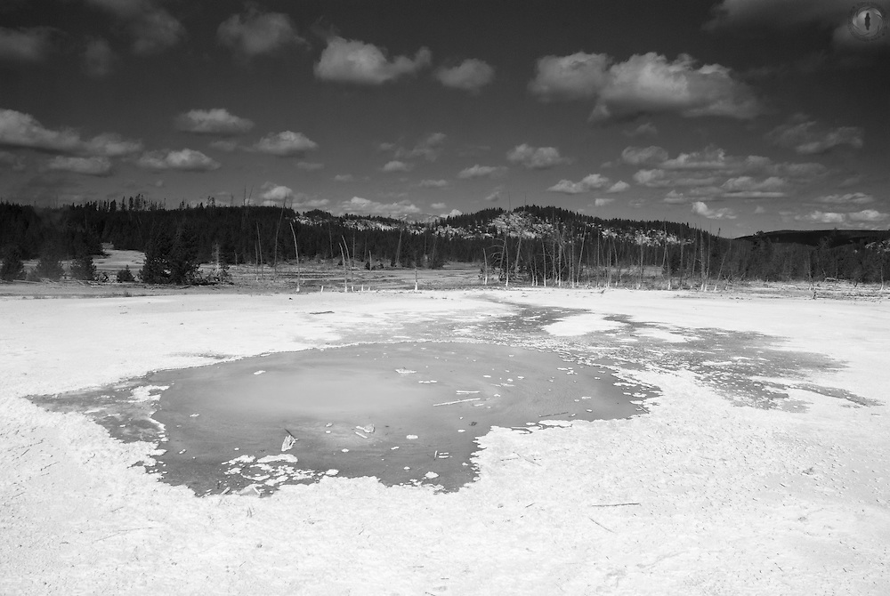 A geothermal pool in the Norris basin in Yellowstone National Park taken in black and white.