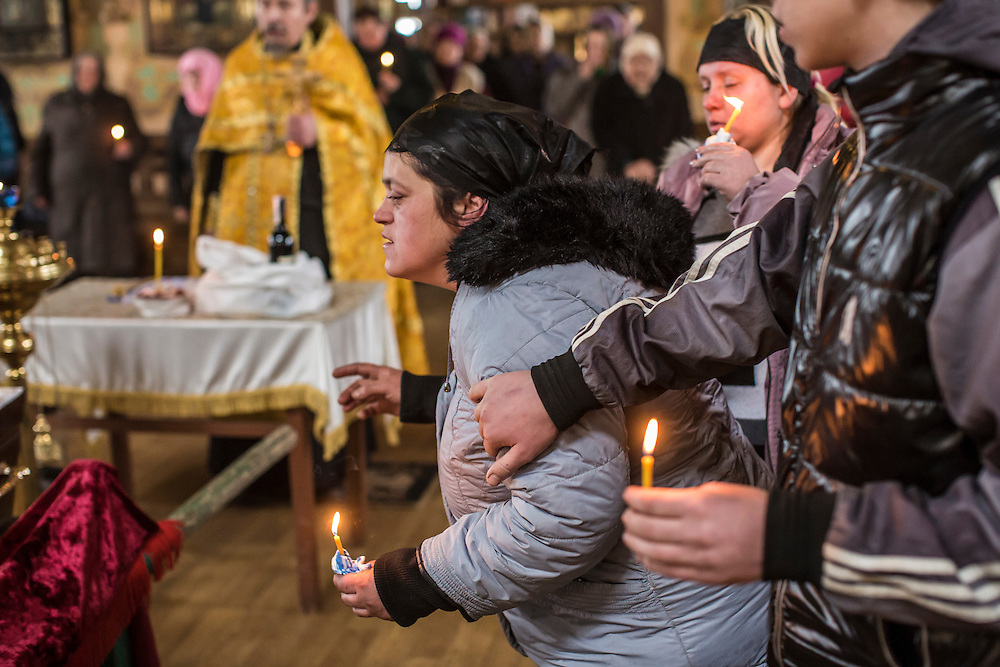 ARTEMIVSK, UKRAINE - FEBRUARY 15: Zhanna Molodetskykh (C) attends the funeral of her son Igor Molodetskykh, 7, who was killed two days prior when a shell hit his school on February 15, 2015 in Artemivsk, Ukraine. A ceasefire scheduled to go into effect at midnight was reportedly observed along most of the front, save for near the embattled town of Debaltseve. (Photo by Brendan Hoffman/Getty Images) *** Local Caption *** Zhanna Molodetskykh