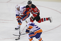 Apr 3; Newark, NJ, USA; New Jersey Devils left wing Ilya Kovalchuk (17) skates with the puck while being defended by New York Islanders center Frans Nielsen (51) and New York Islanders defenseman Mark Streit (2)  during the third period at the Prudential Center.  The Devils defeated the Islanders 3-1.