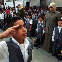 A young boy salutes as the Palestinian flag is raised during the playing of the national anthem at a school in Gaza City. (Photo/Scott Dalton)
