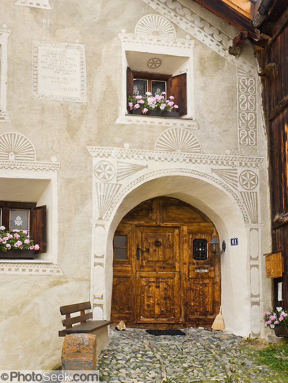 "Cobblestones lead to front door of an historic building decorated with sgraffito (or scraffito, plural: sgraffiti), a technique of wall decor where layers of plaster tinted in contrasting colors are applied to a moistened surface. 17th century Guarda is one of the best preserved and characteristic villages of the Lower Engadine. Visit Guarda in Graubünden canton, Switzerland, the Alps, Europe. The Swiss valley of Engadine translates as the ""garden of the En (or Inn) River"" (Engadin in German, Engiadina in Romansh, Engadina in Italian)."