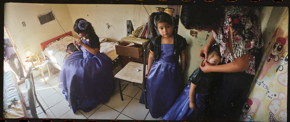 """A mother, center, prepares her daughters for a """"Quinceniera"""" or 15th birthday party at their home in Ciudad Juarez, Mexico in 2010."""