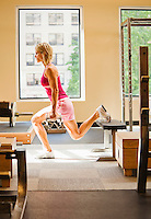A woman doing one legged dumbell squat / lunges in a health club.