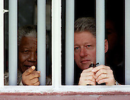 CAP09:SAFRICA-CLINTON:CAPE TOWN,27MAR98 - U.S. President Bill Clinton (R) and South African President Nelson Mandela peer through the bars of the cell in which Mandela spent 17 years while incarcerated by the former South African government. Mandela showed the cell to Clinton during a tour of Robben Island March 27, the penal colony where he was held.  wm/Photo by Rick Wilking    REUTERS