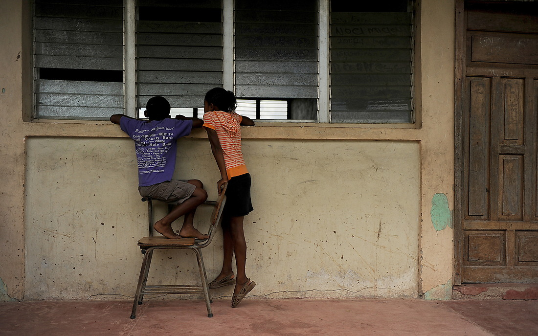 A couple local Honduran children take a peek inside at patients being seen by the U.S. Military medical team in the remote village of Wawina. The medical team used a local schoolhouse as their makeshift clinic. — © /