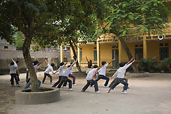 Color film photograph of kids exercising in a school yard, La Phu textile craft village, Hanoi outskirts, Vietnam, Southeast Asia