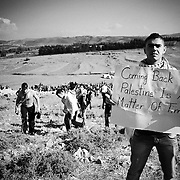 Ahmad, originaly from Acre carries a sign. Tens of thousands of Palestinians and their supporters gathered at the border town of Maroun Al Rass to commemorate 63 years since the Nakba or catastrophe. Palestinians commemorate on May 15 the loss of their homeland.The Lebanese army stated that 10 protesters died due to gunshot wounds by the Israeli Army and 112 were wounded.  Maroun Al Rass, Lebanon, May 15, 2011. OMAR YASHRUTI/PI, PRENSA-INTERNACIONAL.COM