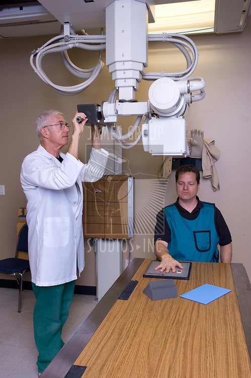 X-ray technician giving a man an x-ray of his hand